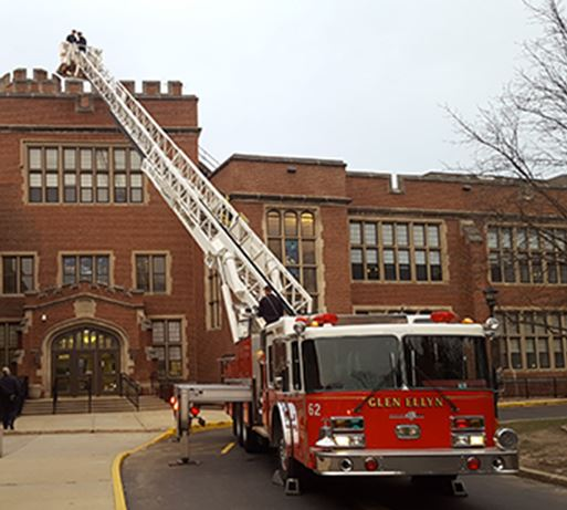 Fire truck ladder raised to roof
